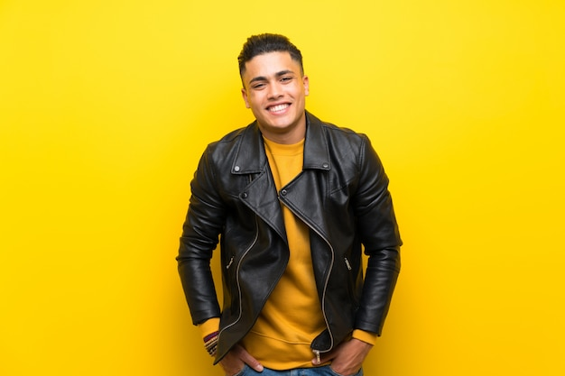 Young man over isolated yellow  laughing
