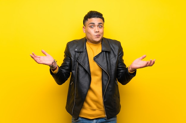 Young man over isolated yellow wall having doubts while raising hands