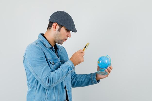 Giovane uomo in giacca, berretto cercando mini globo con lente d'ingrandimento e guardando attento.