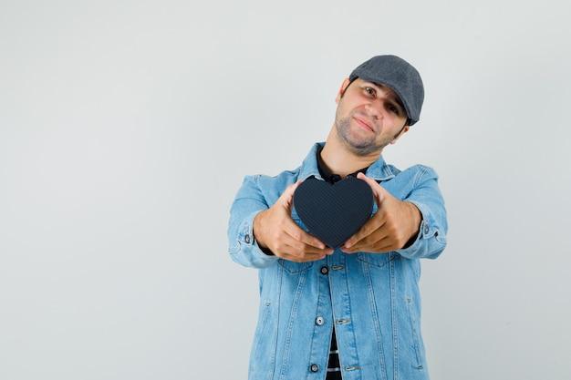 Giovane uomo in giacca, berretto che mostra un regalo a forma di cuore e cerca uno spazio adorabile per il testo