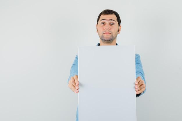 Giovane uomo in giacca che mostra tela bianca e che sembra sorpreso