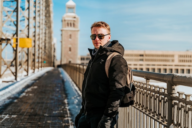 A young man in a jacket walks on a snow bridge in saint petersburg in winter in sunny weather