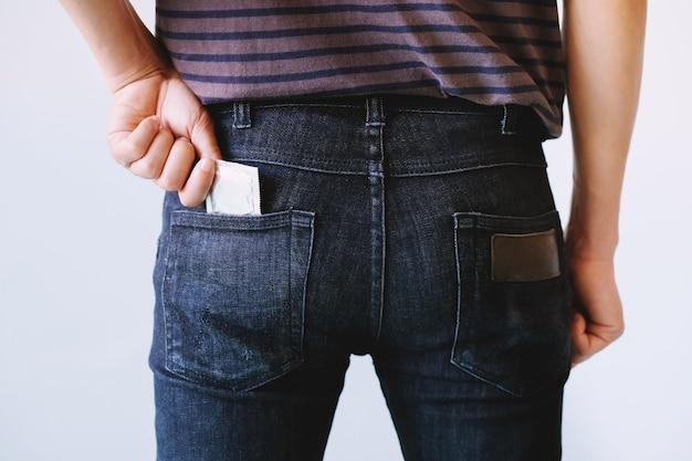 젊은 남자 청바지 뒷면 주머니 청바지에서 콘돔을 손에 들고 콘돔을 수행합니다.
