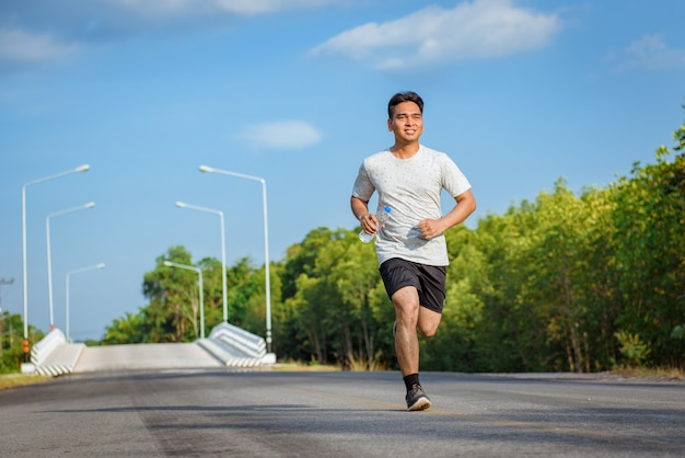 Young man jogger athlete training and doing workout outdoors on street  road