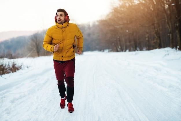 Musucを聞いて雪に覆われた森の中をジョギングする若い男