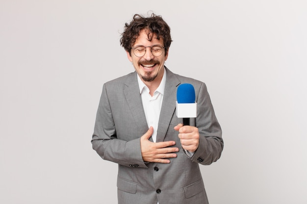 Молодой человек-журналист громко смеется над веселой шуткой