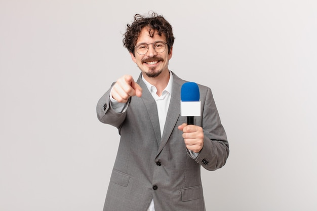 Young man journalist pointing at camera choosing you