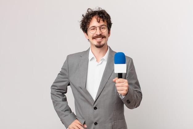 Молодой человек-журналист счастливо улыбается, положив руку на бедро и уверенно