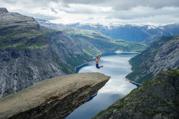 Молодой человек прыгает на край тролльтунга. норвегия.