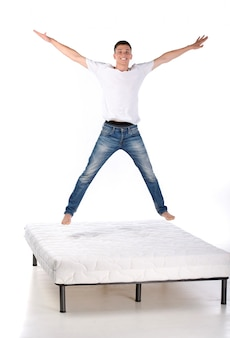 Young man jumping on the big white mattress