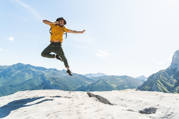 Young man jumping having a phone call on top of a mountain wearing a yellow backpack.