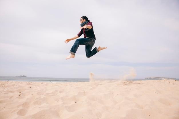 若い男がビーチで分離された砂の上にジャンプ