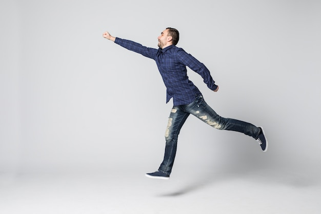 空気中のジャンプと白い背景の上の彼の腕を大きく開いて叫んで若い男