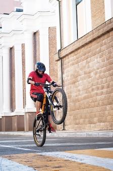 若い男が都市でマウンテンバイクの後輪にジャンプします。