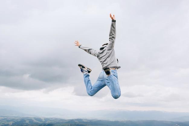 若い男が山の空雲の岩の上に屋外ジャンプ