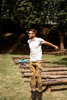 Молодой человек прыгает через деревянные скамейки
