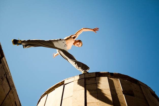 Young man jumping and practicing parkour between buildings roofs outside on clear summer day with blue sky at background