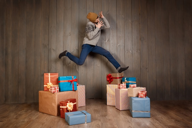 Young man jumping rejoicing among christmas gifts over wooden wall