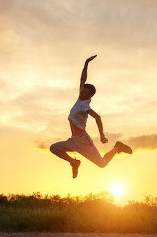 Young man jumping up against the sunset sky