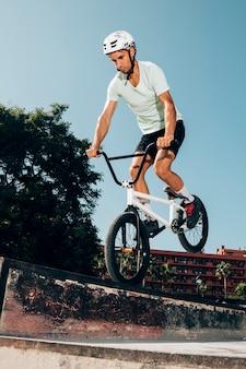 Молодой человек прыгает с велосипедом