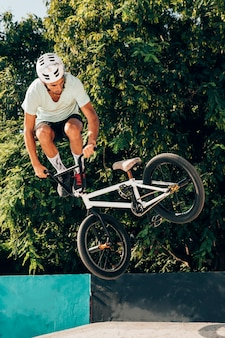 Young man jumping with bmx bike long shot