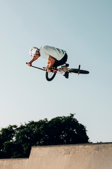 Young man jumping with bmx bike low angle view