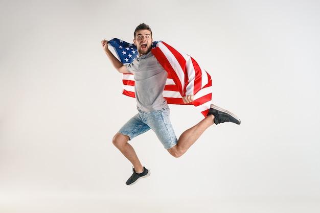 白いスタジオで隔離のアメリカ合衆国の旗を持ってジャンプする若い男。