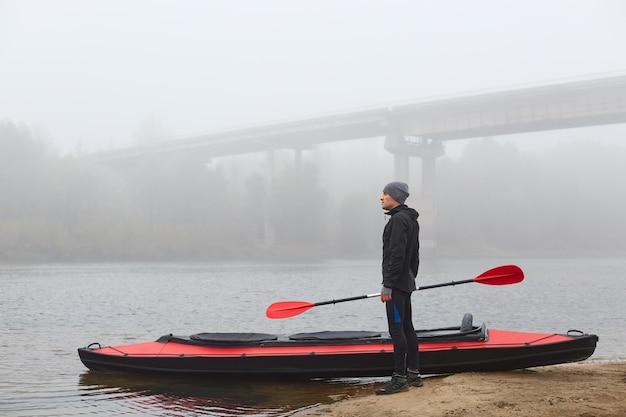 Молодой человек на байдарках стоит на берегу реки с веслом в руках, смотрит вдаль и наслаждается красивым туманным утром