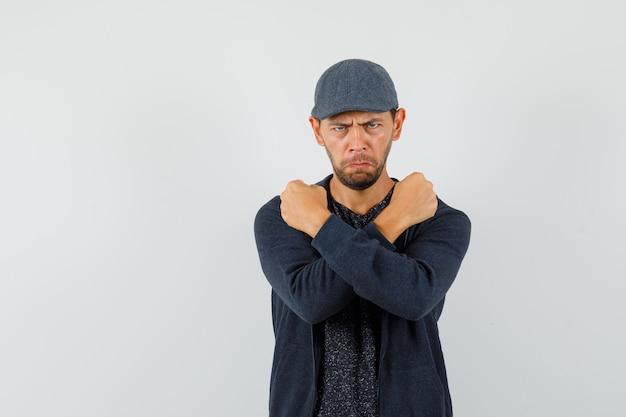 Молодой человек держит скрещенные кулаки на груди в футболке, куртке, кепке и выглядит сердитым. передний план.