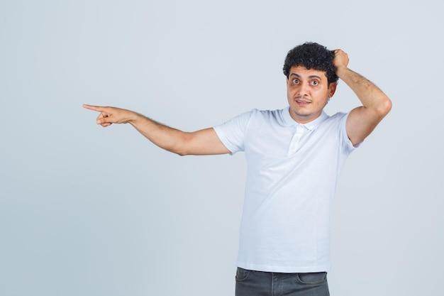 Giovane che tiene la mano sulla testa, indicando da parte in maglietta bianca, pantaloni e sembra perplesso. vista frontale.