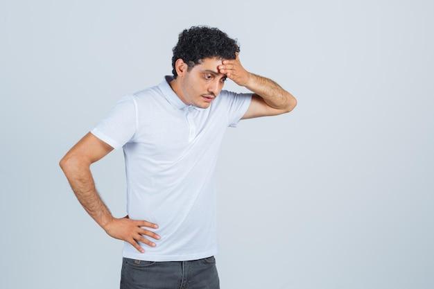 젊은 남자는 흰색 티셔츠, 바지를 입고 이마에 손을 대고 수심에 찬 앞모습을 보고 있습니다.