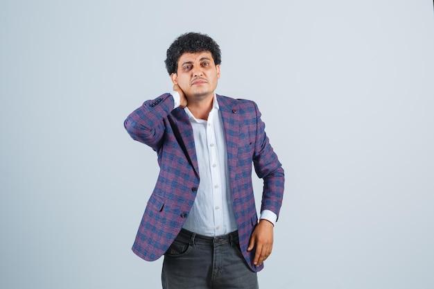 Молодой человек держит руку на шее в рубашке, куртке, штанах и плохо выглядит, вид спереди.