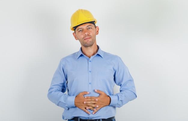 若い男がシャツ、ヘルメットで胃に手を組んで維持