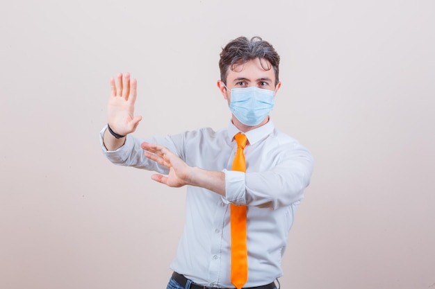 Young man keeping hands to defend himself in shirt, tie, mask and looking worried