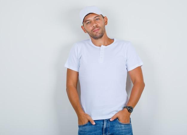 Молодой человек держит руки в кармане джинсов в белой футболке, вид спереди кепки.