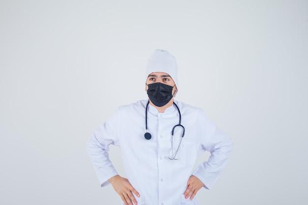 흰색 유니폼, 마스크에 허리에 손을 유지 하 고 사려 깊은 찾고 젊은 남자. 전면보기.