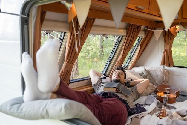 바퀴에 집에서 침대에 누워있는 동안 머리 뒤에 손을 유지하는 젊은 남자