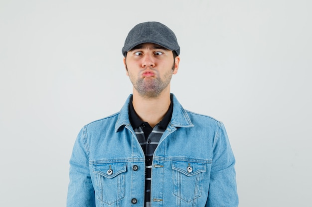 Giovane che tiene le labbra piegate con occhi strabici in t-shirt, giacca, berretto e sembra divertente