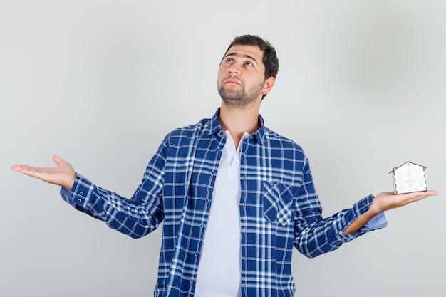 Молодой человек держит открытые руки с моделью дома в рубашке и выглядит обнадеживающим.
