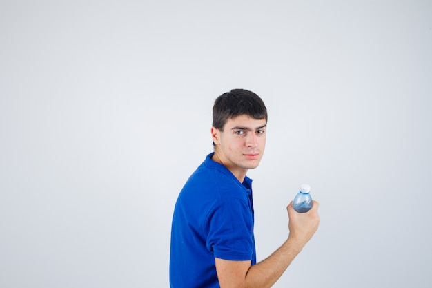 Молодой человек держит пластиковую бутылку в футболке и выглядит уверенно.
