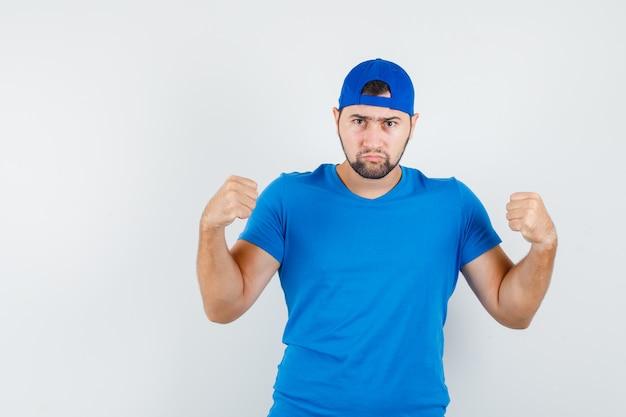 Молодой человек держит поднятые кулаки в синей футболке и кепке и выглядит серьезным