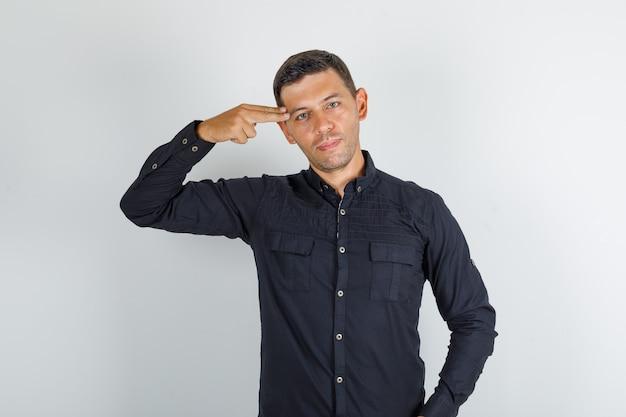 黒いシャツの寺院に2本の指を保つ若い男