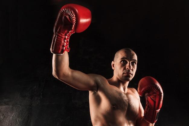 Young man kickboxing on black