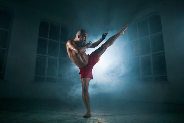 Young man kickboxing in blue smoke