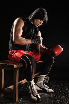 The young  man kickboxing lacing glove