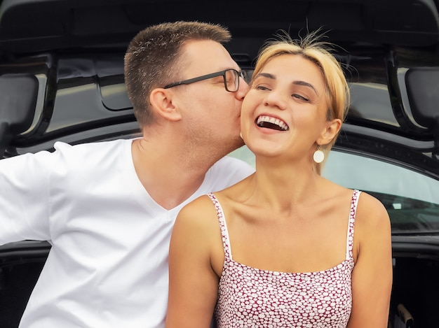 若い男は笑顔の幸せな女の子、車の近くで恋をしているカップル、夏の時間にキスします