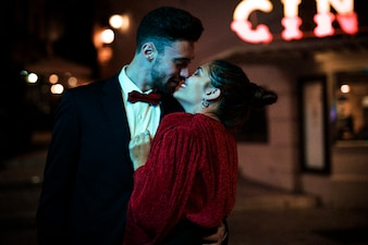 Young man kissing and hugging charming attractive happy woman on street