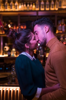 Young man kissing and embracing with woman near bar counter