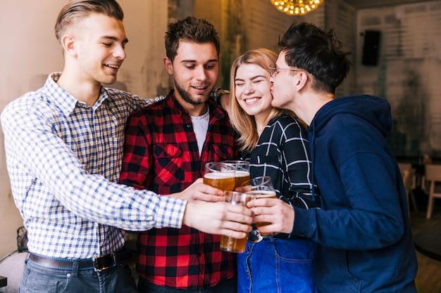 若い男が友達とビールのグラスを乾杯しながら彼女のガールフレンドにキス