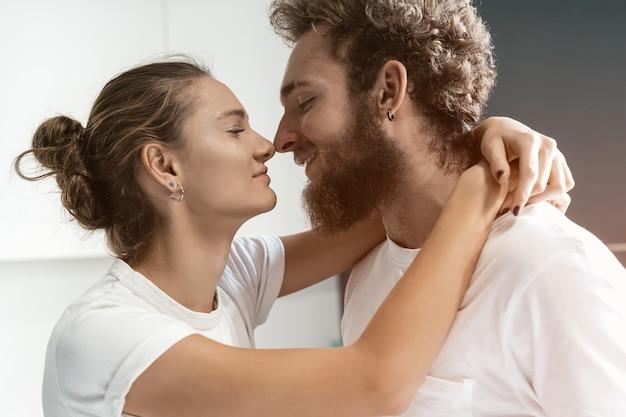 Молодой человек целует свою жену, стоя на кухне.